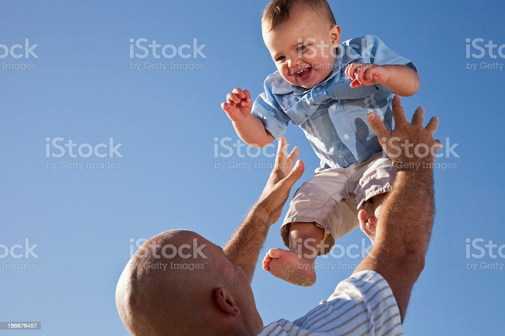 Father tossing little boy in air royalty-free stock photo