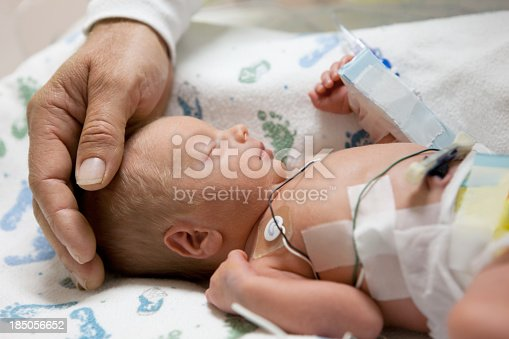 istock father touching head of a premature baby in incubator 185056652