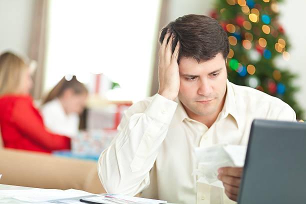 padre cercando di pagare le bollette di natale con famiglia dietro di lui. - holiday and invoice family foto e immagini stock