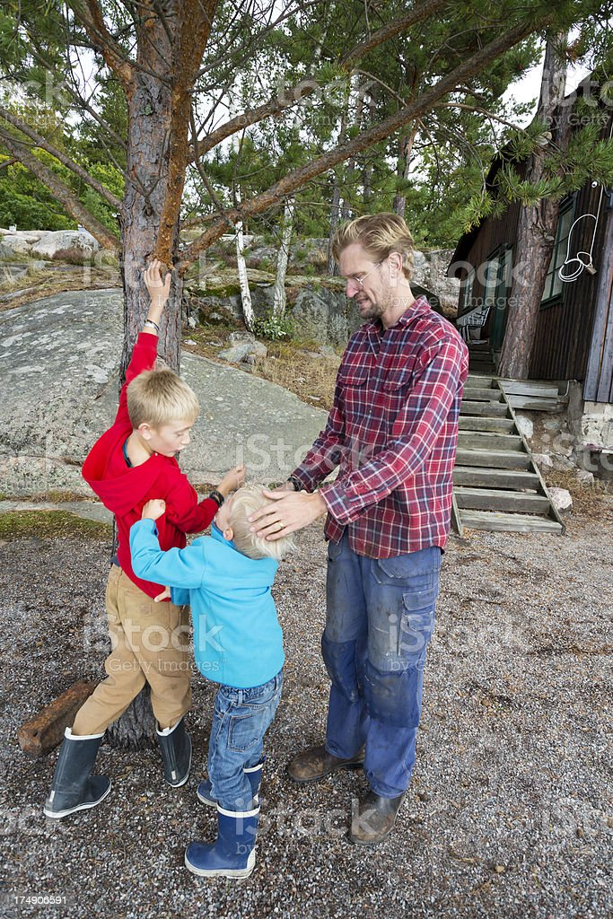 Father trying to quite down his fighting little boys. stock photo