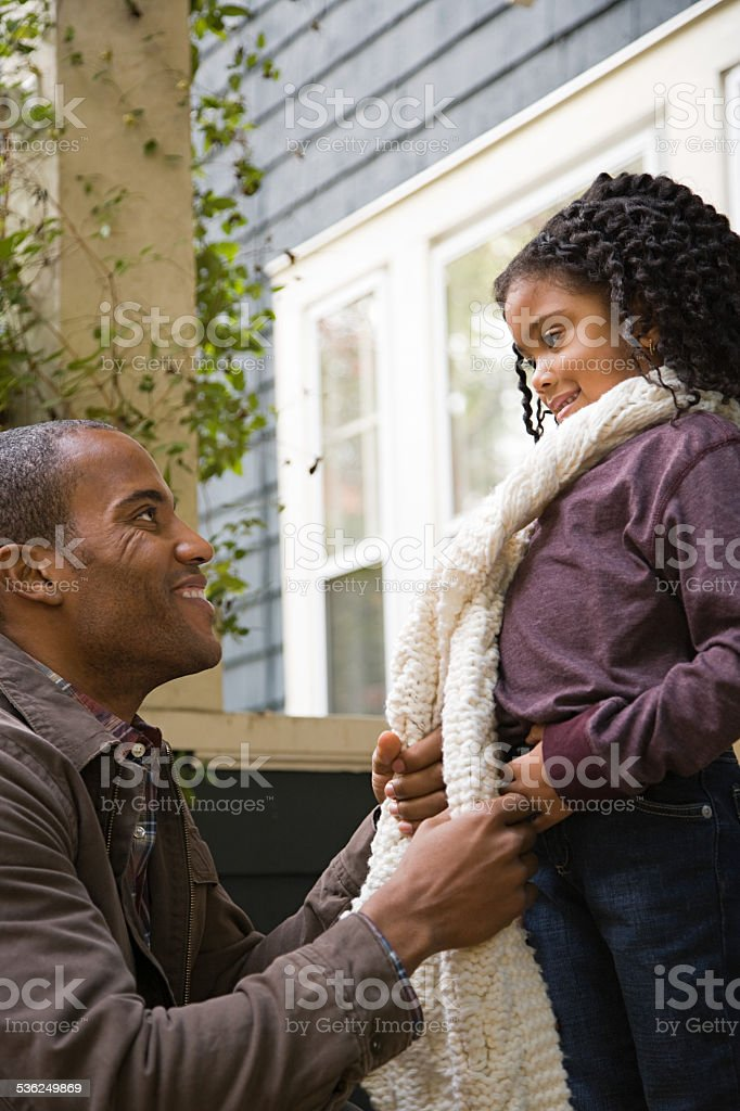 Father tying daughters scarf stock photo