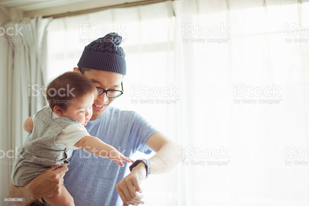 Father using a smart watch at home. stock photo