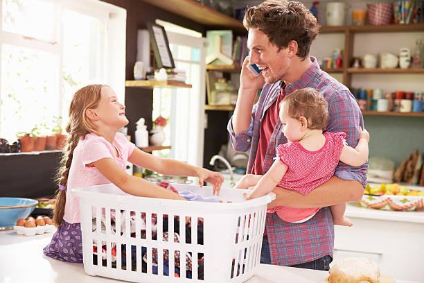 padre mediante teléfono móvil como él mismo tipo lavandería con niños - padre que se queda en casa fotografías e imágenes de stock