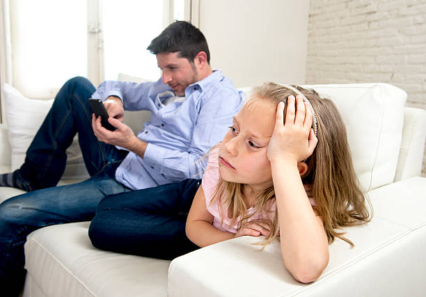 father using mobile phone ignoring little sad daughter bored - kids online abuse stockfoto's en -beelden