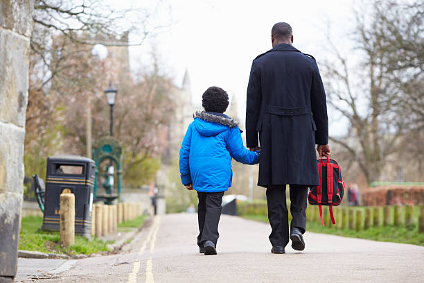 Father Walking Son To School Along Path stock photo