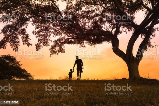 Photo of Father walking with is son at the park at sunset
