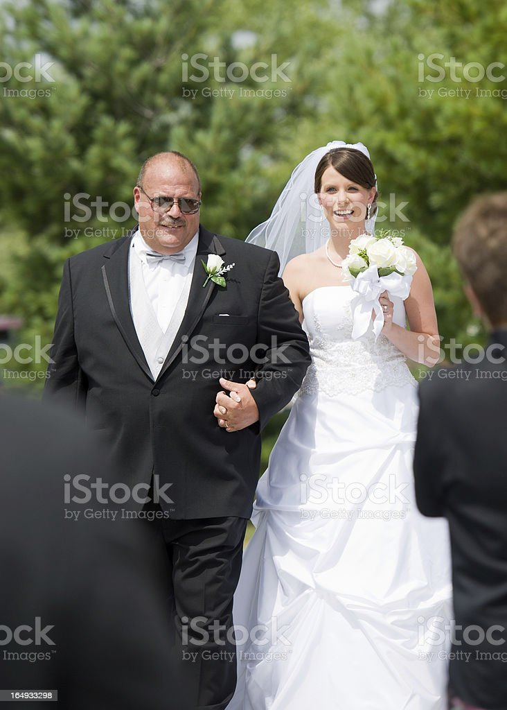 Father walks bride down the isle at outdoor wedding stock photo