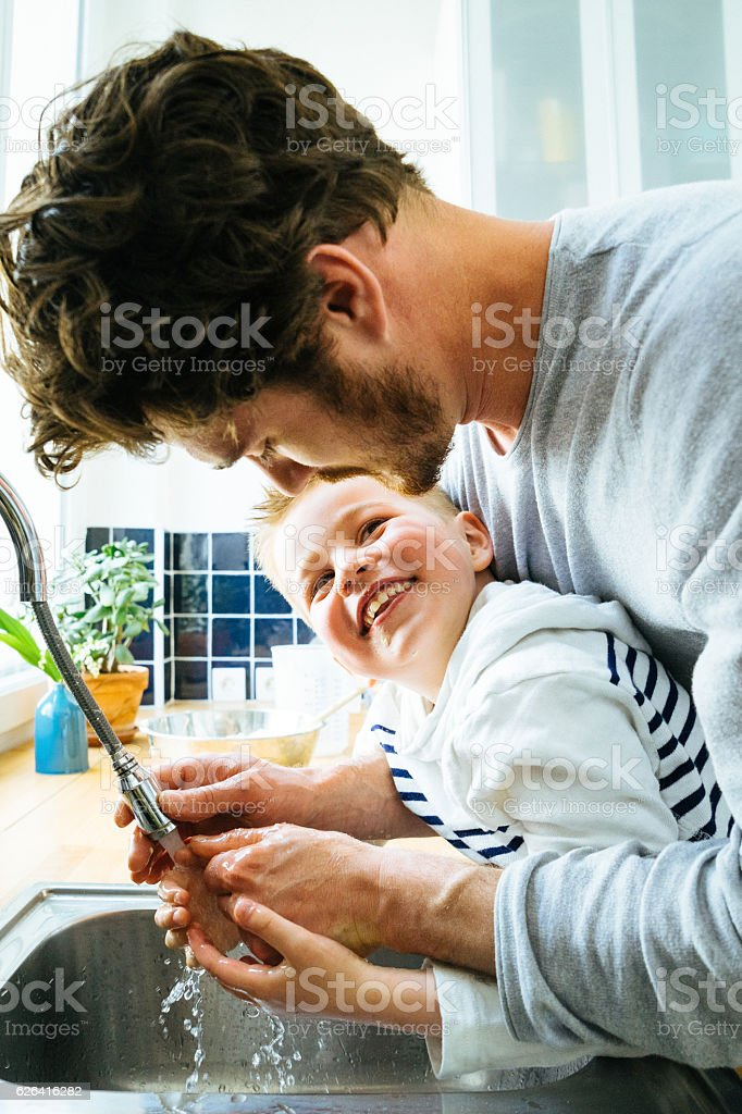 Father Washing Sons Hands In Kitchen Sink After Cooking Together stock photo