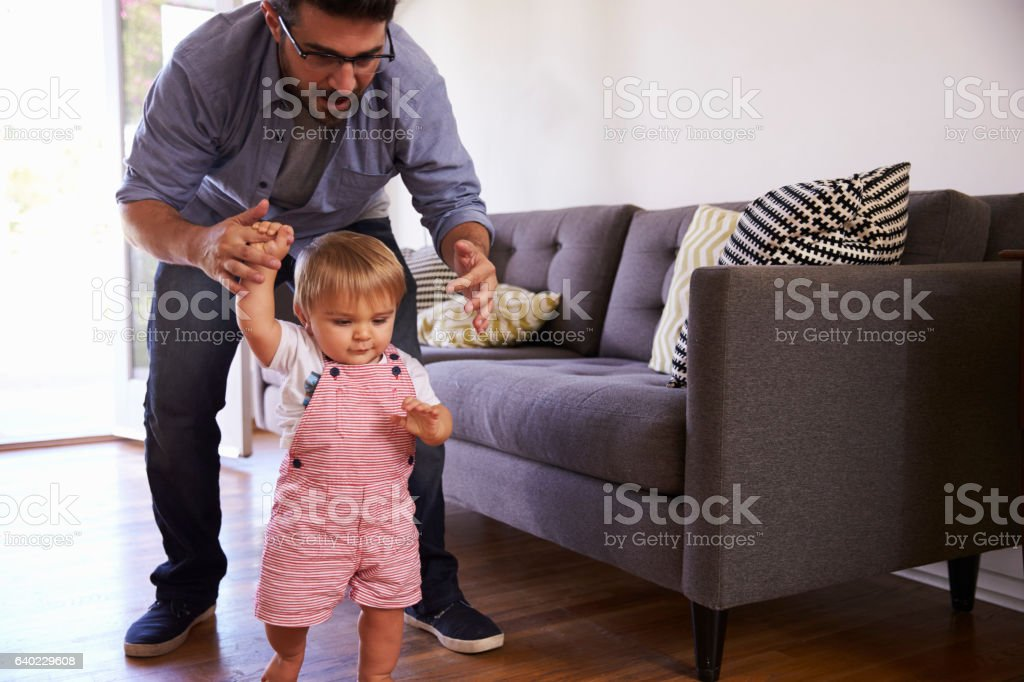 Father Watching Baby Daughter Take First Steps At Home stock photo