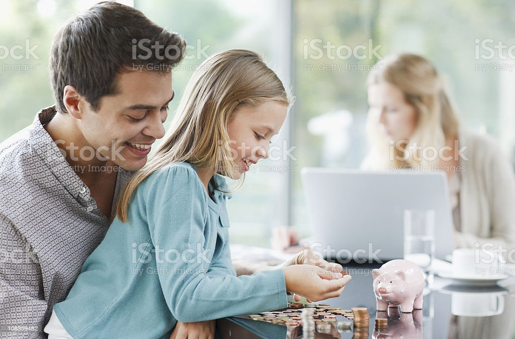 Father watching daughter count coins stock photo