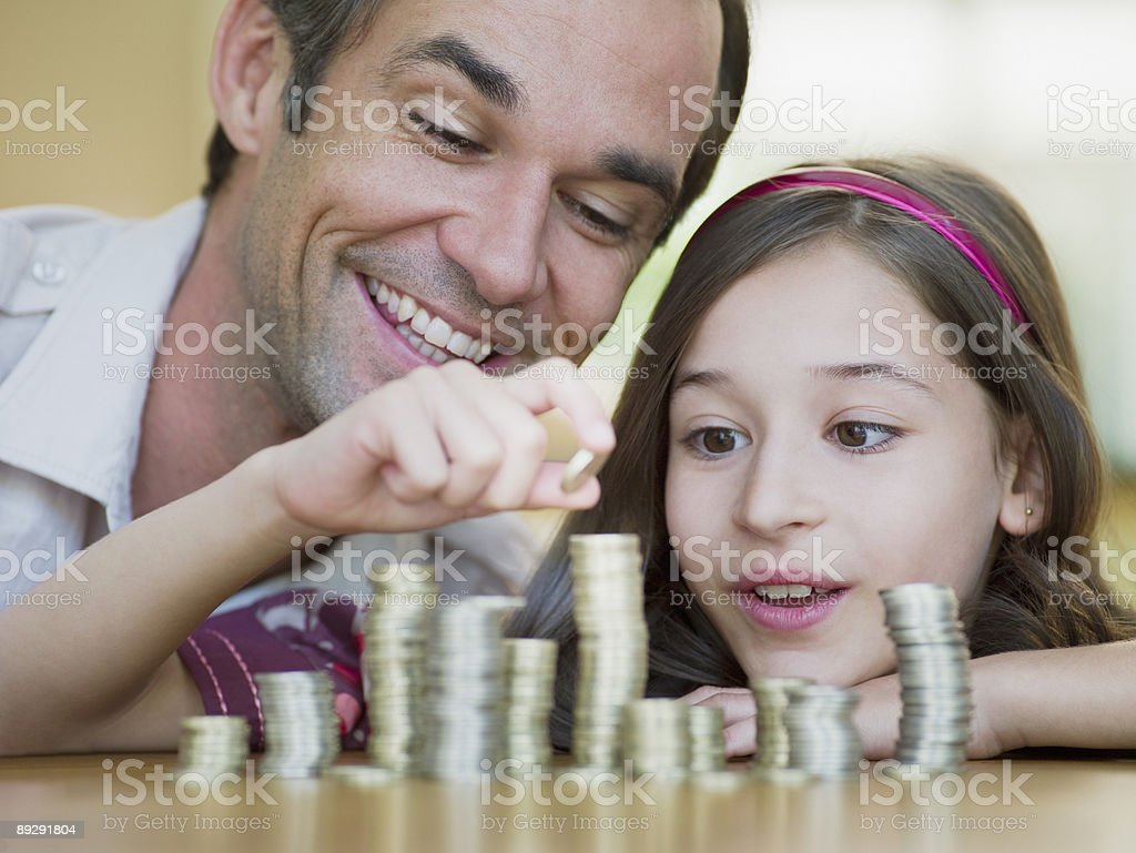 Father watching daughter stack coins royalty-free stock photo