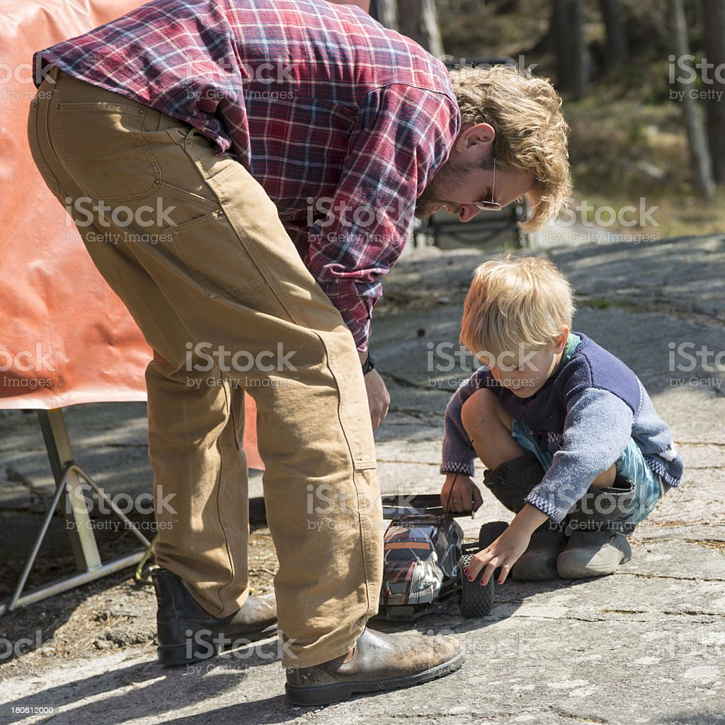Father watching small son playing with car. stock photo