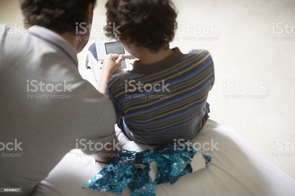 Father watching son play Christmas video game royalty-free stock photo