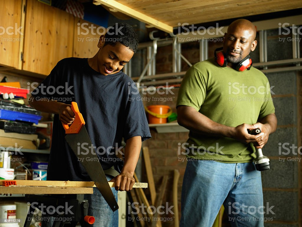 Father watching teenage Son sawing wood royalty-free stock photo