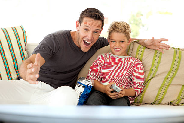 Father watching TV with Son stock photo