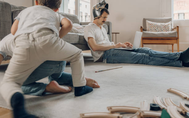 Father wearing a helmet trying to work from home Father wearing a helmet trying to work from home messy home office stock pictures, royalty-free photos & images