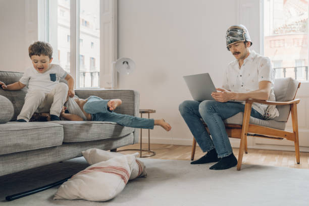 Father wearing a helmet trying to work from home stock photo