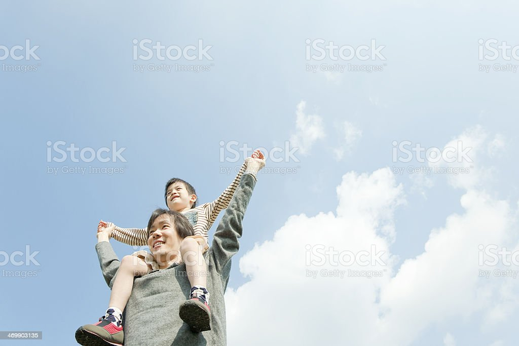 Father who carries a child on his shoulders stock photo