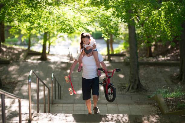 vater, der eine schulter-tochter nimmt - fahrradträger stock-fotos und bilder