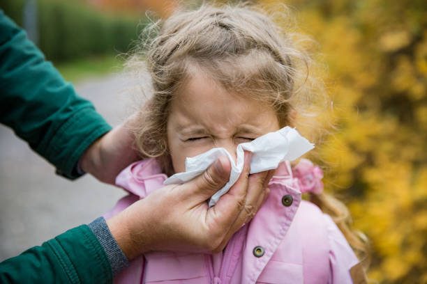 Father wiping daughter's nose with handkerchief Father wiping daughter's nose with handkerchief. Sick little girl with cold and flu standing outdoors. Preschooler sneezing, coughing, having runny red nose. Autumn street background flu stock pictures, royalty-free photos & images