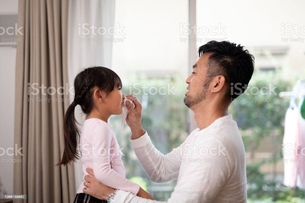 父の家で彼の娘の鼻を拭く ストックフォト