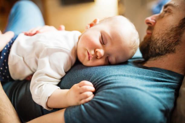vater mit einem baby girl zu hause schlafen. - genderblend stock-fotos und bilder