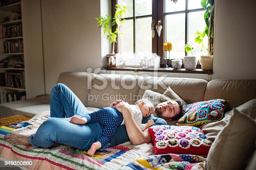 istock Father with a baby girl at home sleeping. 949350860