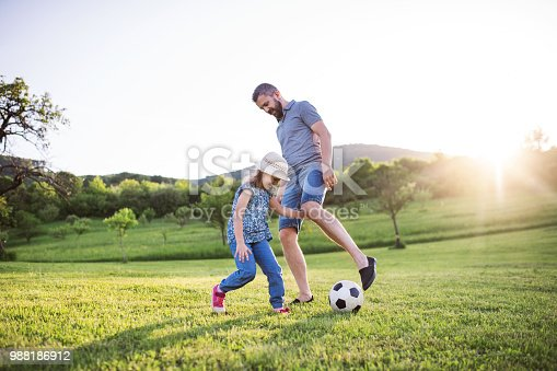 istock Father with a small daughter playing with a ball in spring nature. 988186912