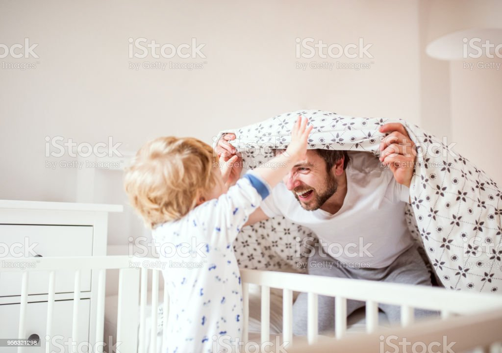 Father with a toddler boy having fun in bedroom at home at bedtime. stock photo