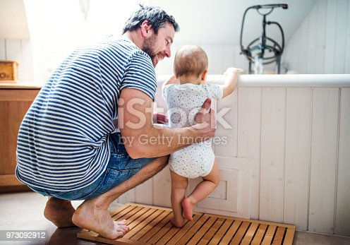 Father with a toddler child at home standing by the tub in the bathroom. Paternity leave.