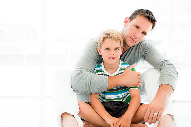 Father with arm around his son stock photo