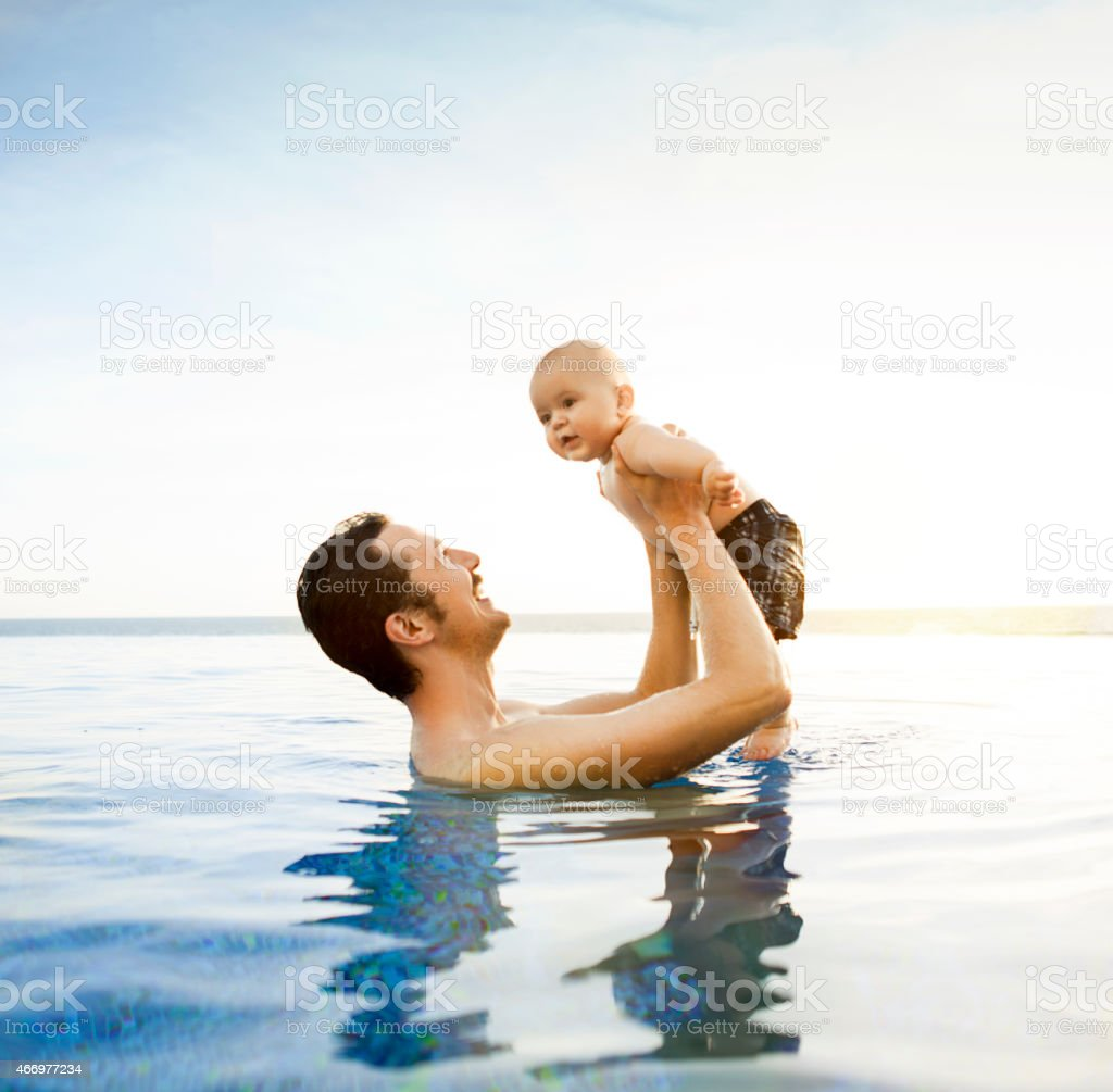 Father with baby boy in swimming pool stock photo
