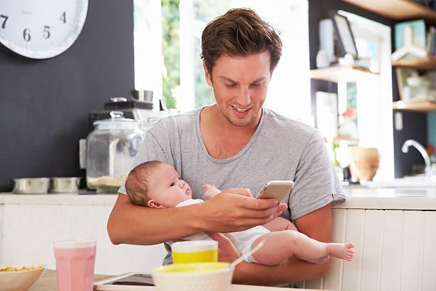 vater und baby-tochter, die ein handy in der küche - hausmannskost stock-fotos und bilder