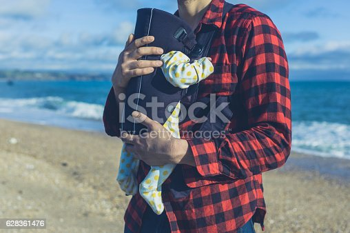 A young father is carrying his baby in a carrier on the beach