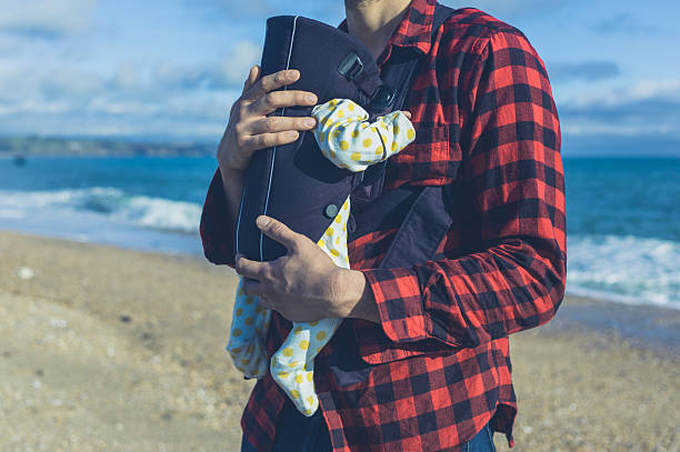 Father with baby in carrier on beach stock photo