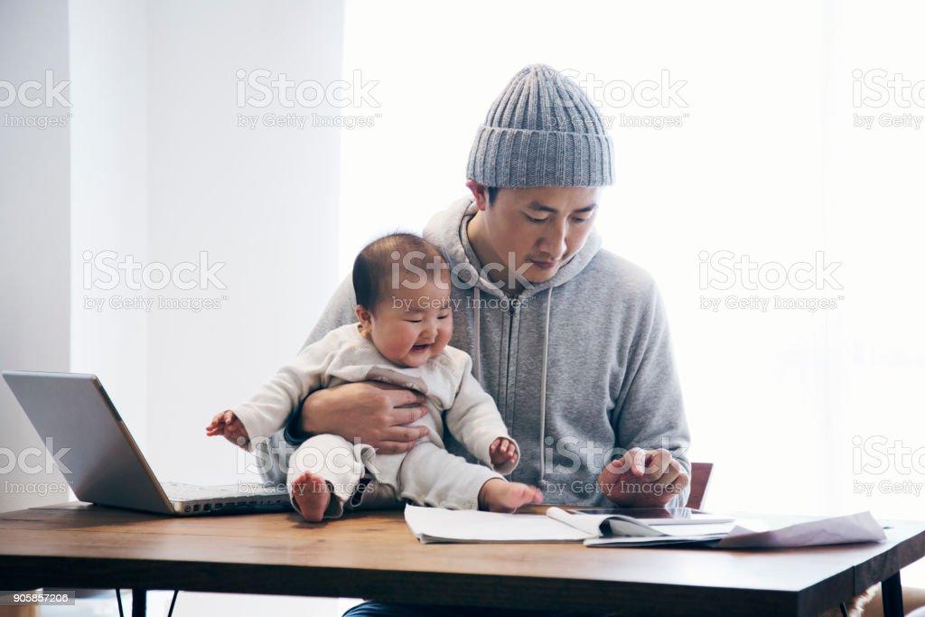 自宅で仕事の赤ちゃんと父親 ストックフォト