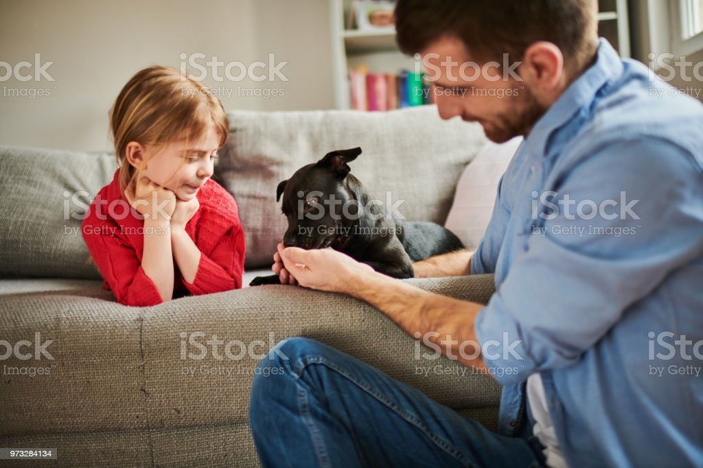 Father and daughter at home playing with their black puppy dog.