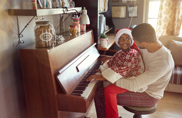 father with child girl on Christmas play music on piano. concept of holidays and family happiness. stock photo