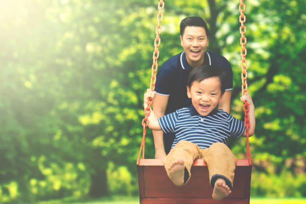 vater mit kind spaß im park - kind schaukel stock-fotos und bilder