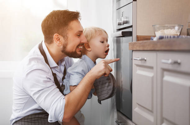 father with   child   son prepares meal, bakes cookies - cooker happy imagens e fotografias de stock