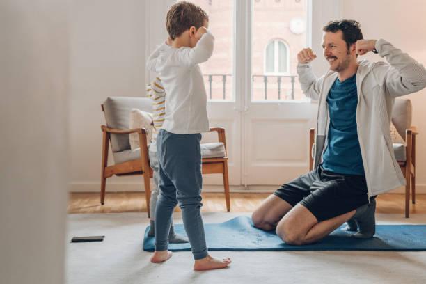 Vater mit Kindern trainiert zu Hause – Foto