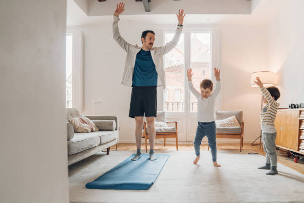 Father with children exercising at home stock photo