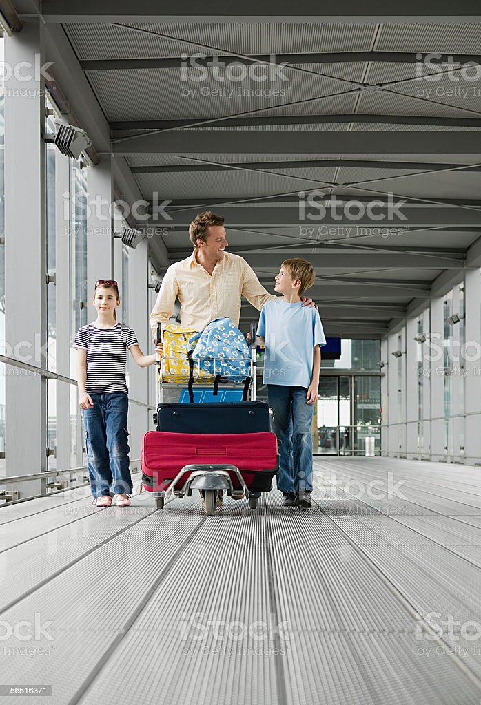 Father with children in airport royalty-free stock photo