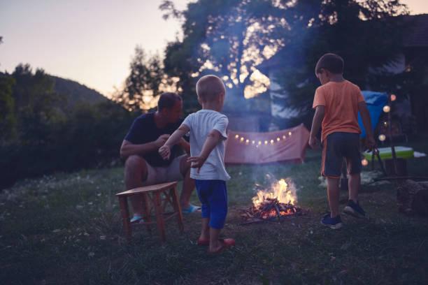 Vater mit Kindern, die ein Campingfeuer im Hinterhof machen. – Foto