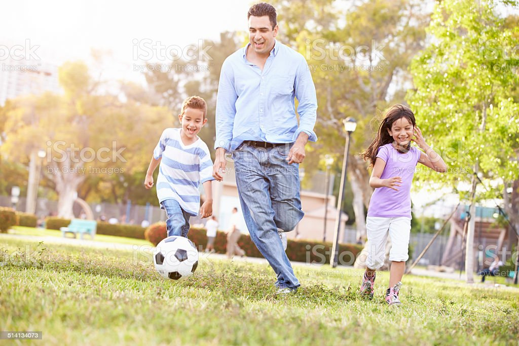 Father With Children Playing Soccer In Park Together stock photo