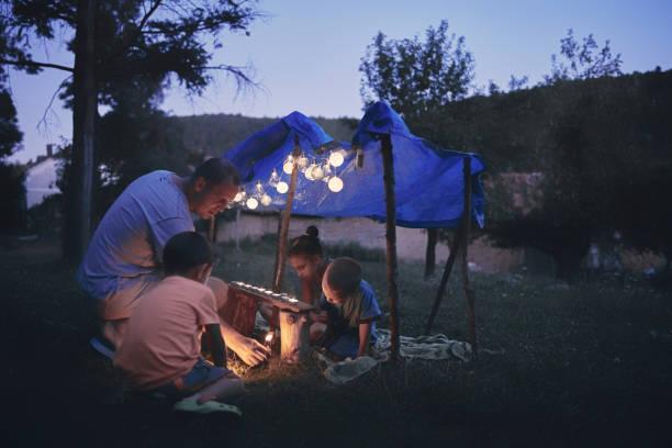 Vater mit Kindern, die unter ihrem Hinterhofzelt spielen. – Foto