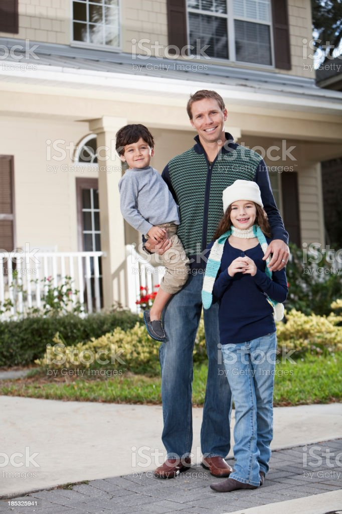 Father with children standing in front of house royalty-free stock photo