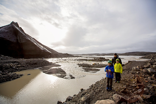 Father with children, walking on a path in beautiful nature of Skaftafell Glacier national park on a gorgeous autumn day