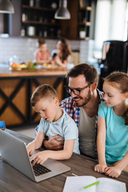 Father with daughter and son on his lap using laptop at home stock photo