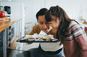 Father with daughter baking cookies together in the kitchen and smelling freshly baked cookies straight from the oven